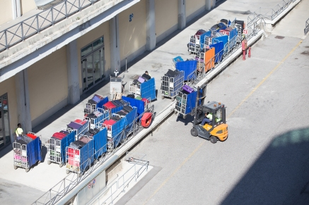 Forklifts loading baggage carts onto the ship.